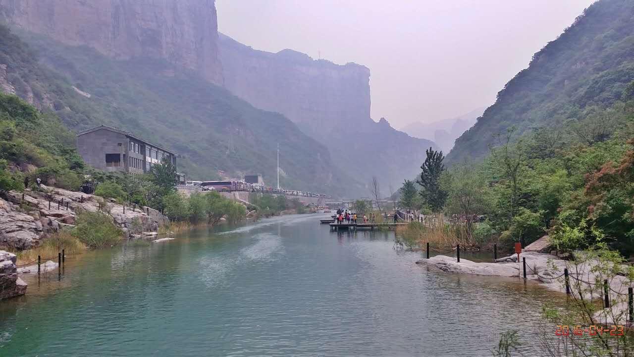 山势巍峨,植被繁盛,栈道镶嵌在岩壁上,绿山掩映在青山里,绿水悠悠